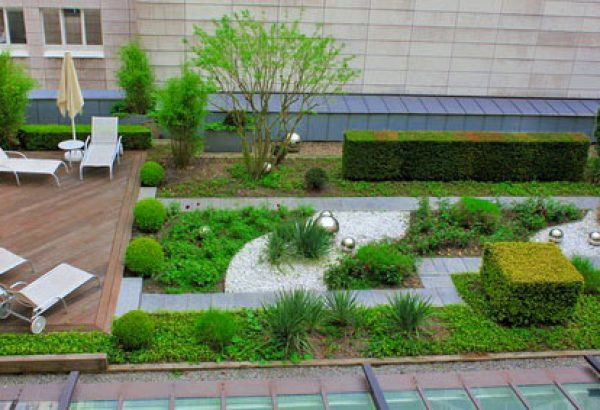 Roof garden with green plants and silver which balls and wooden